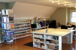 view of cutting table, fabric and ribbon shelf