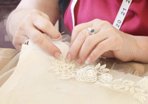 Angee hand sewing and hand beading Alencon lace and freshwater pearls onto a clutch bag